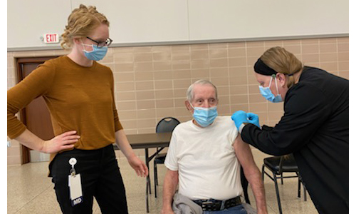 Carpenters Wellness Center primary care physician Dr. Tina Trost, MD is shown above, left with her grandfather, 64-year member of Local 1310, Charles Bosslet, receiving his first dose in the series of the Moderna vaccine by Medical Assistant, Kay Hanse